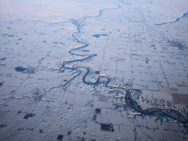Aerial view of river cutting through snowy fields — Stock Photo