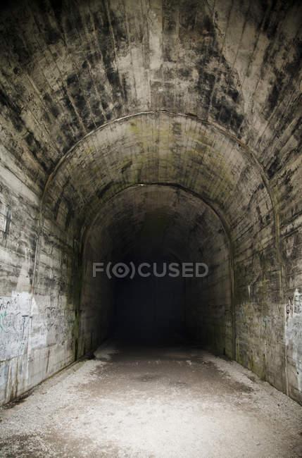 Diminishing view of dark concrete tunnel — Stock Photo