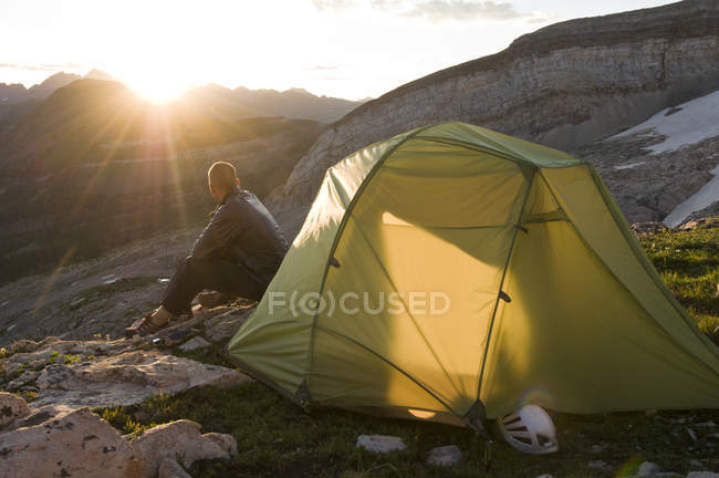 Homme de sunrise bénéficiant à côté de la tente alors qu'il campait dessous de montagne au Trésor en forêt nationale de White River à l'extérieur de marbre, Colorado — Photo de stock