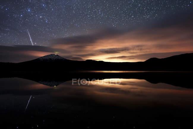Метеор легкий хвост в звездное небо, отражая в озере лавы — стоковое фото