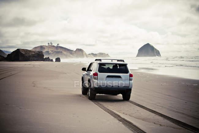 Carro, dirigindo-se ao longo da praia arenosa, Oregon — Fotografia de Stock