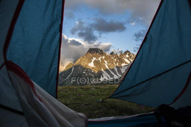 Vue sur les montagnes aux sommets enneigés au rayonnement solaire à travers de la porte de la tente — Photo de stock