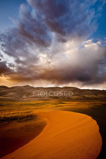 Dunes de sable en fin de soirée la lumière sous le ciel orageux — Photo de stock