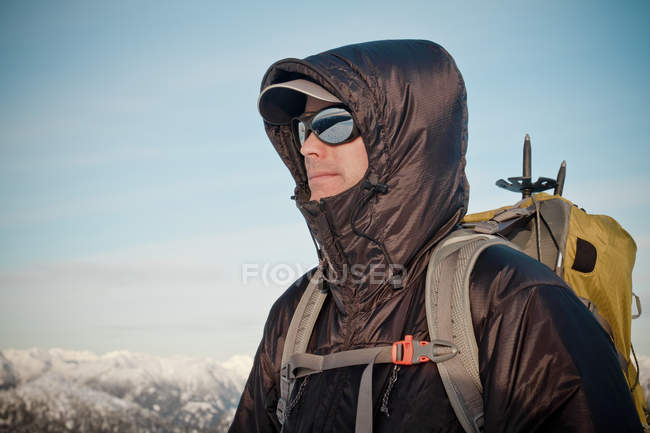 Man wearing warm clothes, sunglasses and backpack — Stock Photo