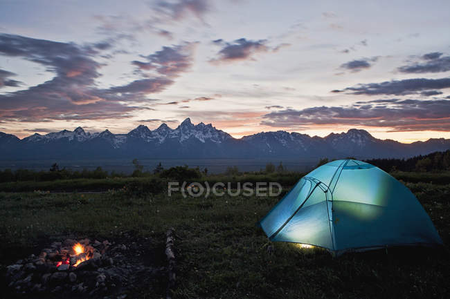 Tenda e falò illuminano al tramonto in Tetons, Wyoming — Foto stock