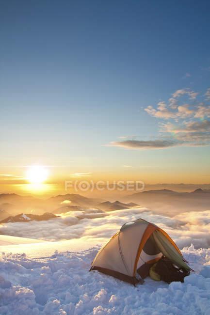 Zelt aufgestellt auf Hügel während des Sonnenuntergangs mit Steinen auf Hintergrund — Stockfoto