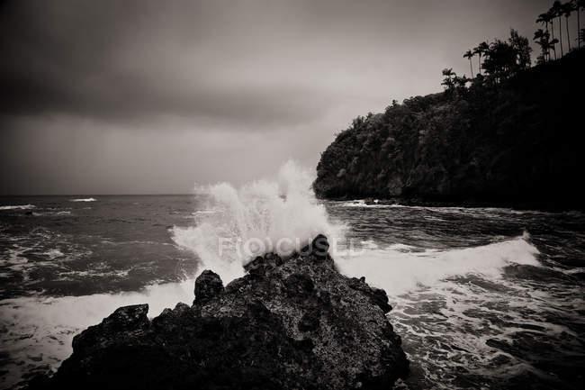 Серфинг волны брызг вверх на скалах на берегу — стоковое фото