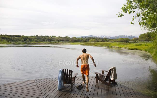 Jovem homem correndo no cais de madeira em direção a lagoa pequena em dia nublado. — Fotografia de Stock