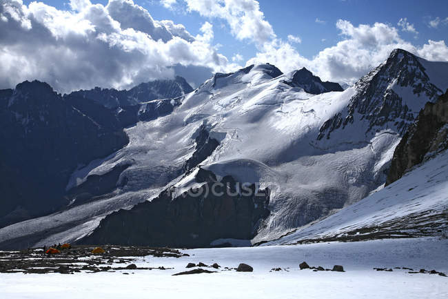 Snowcapped mountains with blue cloudy sky in sunlight — Stock Photo