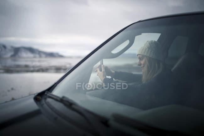 Junge Frau, die schneereichen Winter Wüste aus dem Auto fotografieren — Stockfoto