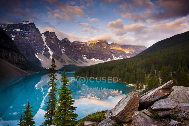 Moraine Lake with mountains and woods under sunset sky — Stock Photo