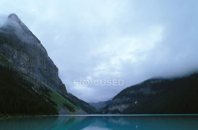 Calmo lago Louise, com montanhas e nuvens baixas — Fotografia de Stock