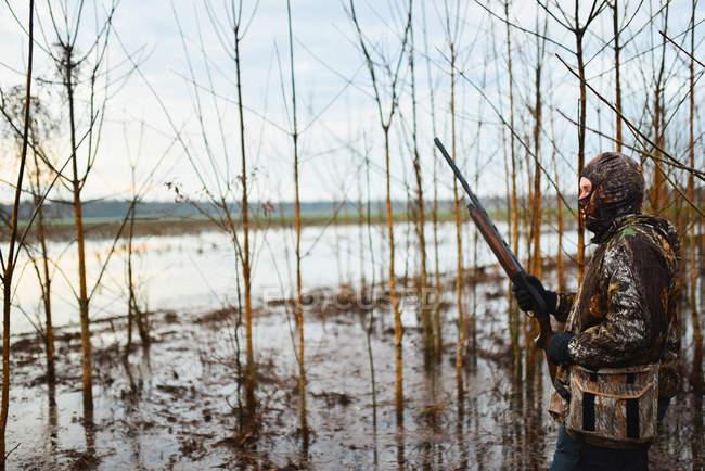 Hombre de pie con el fusil en el campo de Central Alabama, patos en espera al amanecer - foto de stock