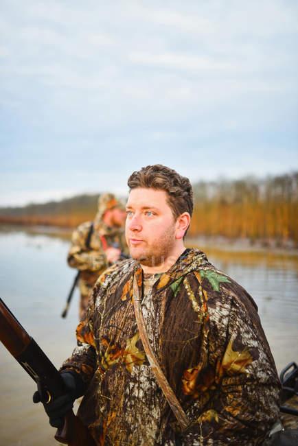 Hombres de pie en el siguiente campo caza un pato temprano en la mañana en Alabama Central - foto de stock