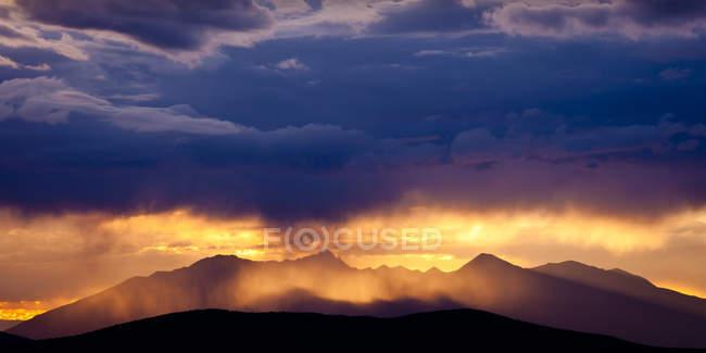 Rocky Mountains mit Regen glühenden Sonne und Wolken — Stockfoto