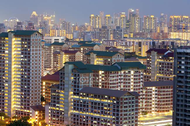 Paisaje urbano con las ventanas iluminadas de edificios en la noche - foto de stock