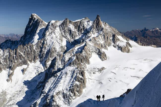 Vista do sol iluminado montanhas com caminhadas pessoas — Fotografia de Stock