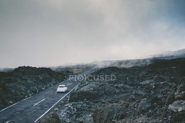 Автомобіль їде на Туманний шлях посеред вулканічних порід — стокове фото