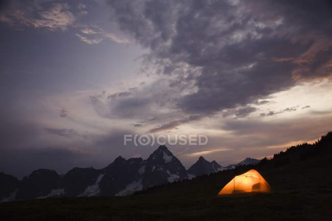 Tente posée par l'éclairage de la chaîne de montagnes d'à l'intérieur — Photo de stock