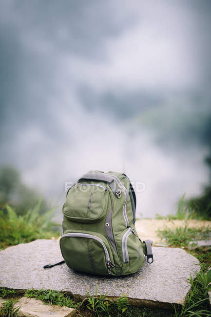 Travel backpack on hill with blurred clouds — Stock Photo