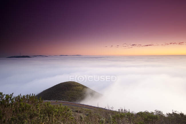 Purple sunset sky above green hill surrounded by clouds — Stock Photo