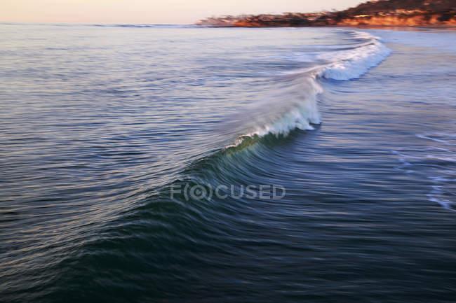 Brechende Welle im Abendlicht, verwischt Bewegung — Stockfoto