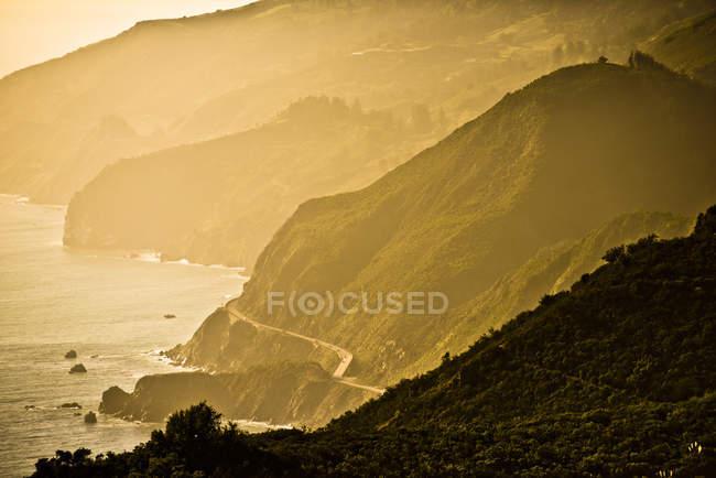 Скалистое побережье с горной дороге, тонированные картина — стоковое фото