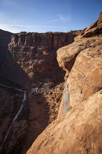 Side view of woman base jumping in Kane Creek area, Moab, Utah. — Stock Photo