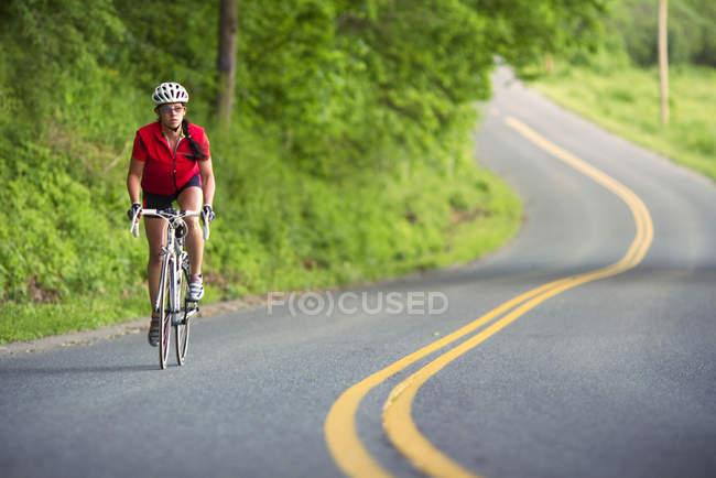 Mujer ciclista caballo largo sinuoso camino de país en colinas del oeste de Massachusetts - foto de stock