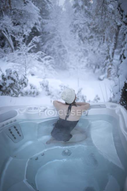 Junge Frau mit Hut blickt vom Whirlpool in den verschneiten Wald — Stockfoto