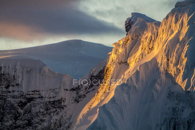 Snowcapped mountain with sunset light and cloudy sky — Stock Photo