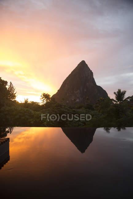 Silueta de las montañas rocosas en el cielo del atardecer con reflejo en el agua - foto de stock