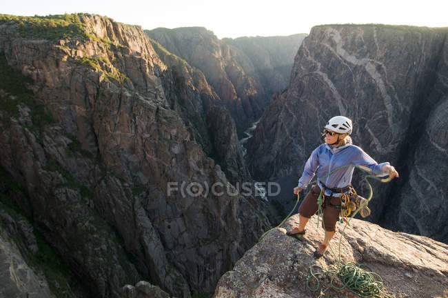 Woman standing on edge of cliff at sunset pulling up rope after rock climbing in South Rim of Black Canyon, Gunnison National Park, Montrose, Colorado — Stock Photo