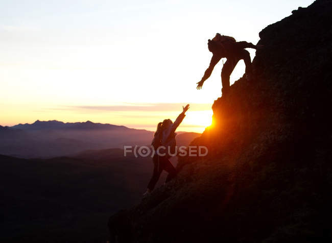 Man helping woman stepping section while hiking in Saddle Mountain State Park, OR — Stock Photo