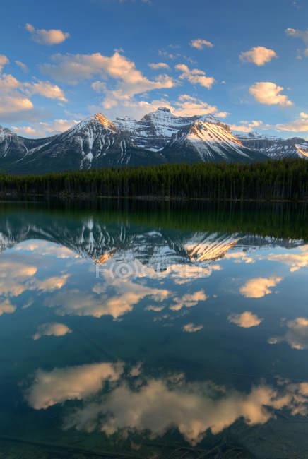 Gama de la montaña y el sol enciende las nubes que reflejan en el lago de Herbert - foto de stock