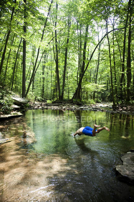 Людина зануритися в невеликий плавальний отвір, Blue Hole Alleghany гори — стокове фото
