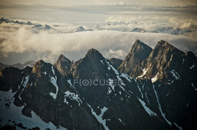 Заснеженные горы с облаками в солнечном свете — стоковое фото
