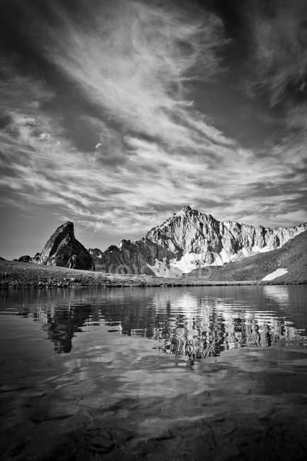 Rocas que reflejan en el agua del lago bajo cielo nublado - foto de stock