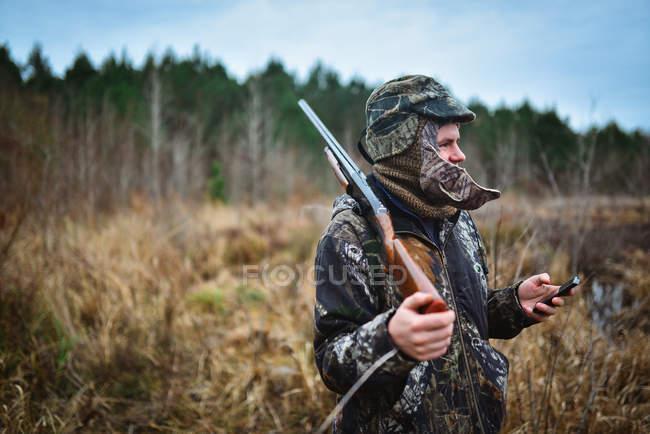 Hombre en espera de inicio de caza de pato y comprobación de teléfono en Alabama Central - foto de stock