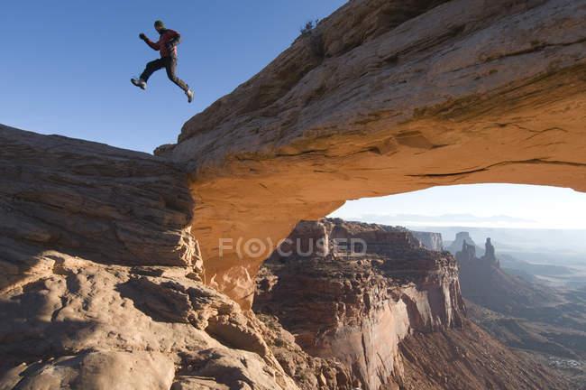 Alpinista masculina pulando de Mesa Arch no Parque Nacional Canyonlands, Moab, Utah — Fotografia de Stock