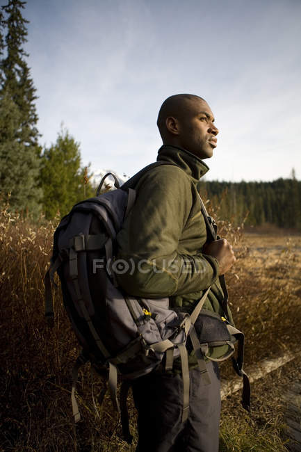 Hiker with backpack standing in brown grass during mountain hike near Mt. Hood in Oregon — Stock Photo