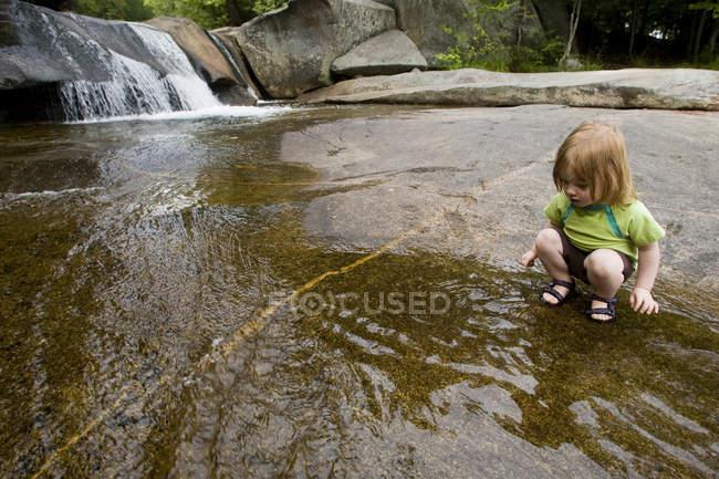 Menina brincando na água ao lado da cachoeira em Newry, Maine — Fotografia de Stock