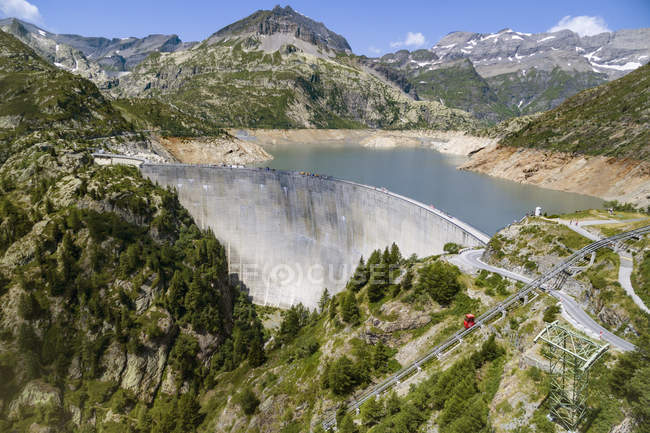 View of emosson dam surrounded by hills covered in green — Stock Photo