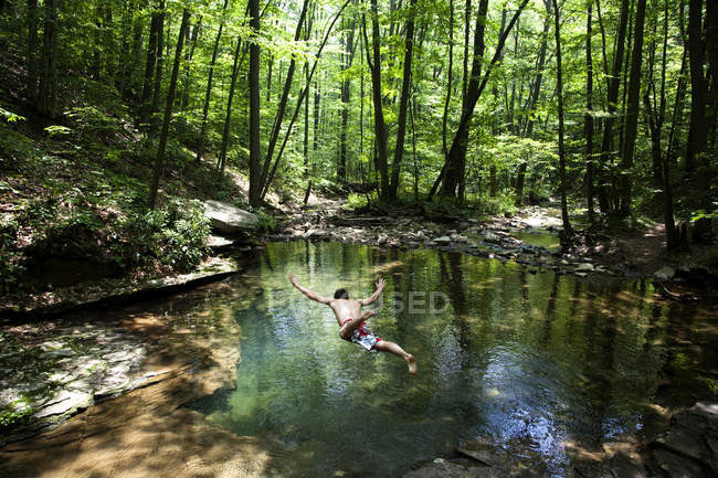 Молода людина падає в невеликий плавальний отвір в оточенні зелені дерева — стокове фото
