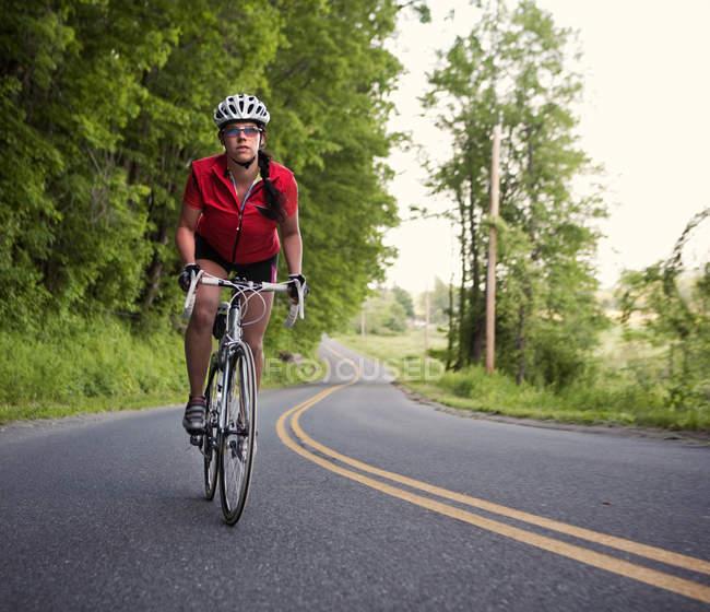 Mujer ciclista en camino rural en el oeste de Massachusetts - foto de stock