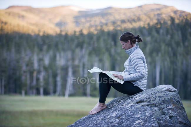 Женщина сидит на валун в большой луг и чтения Топографическая карта — стоковое фото