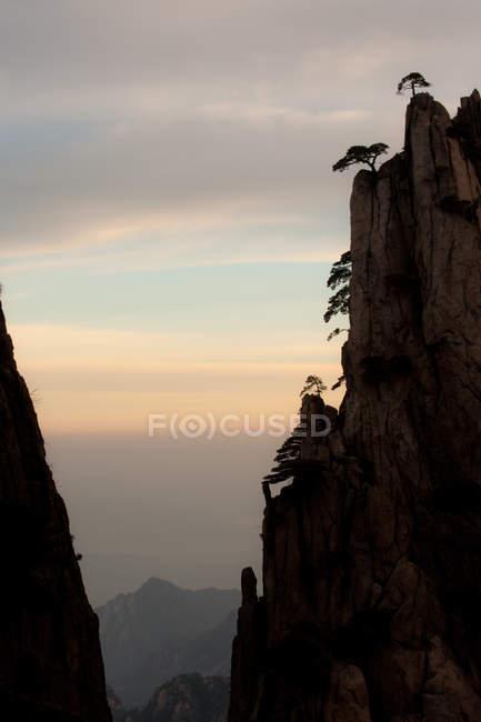 Cliff com árvores e céu ao nascer do sol no fundo — Fotografia de Stock
