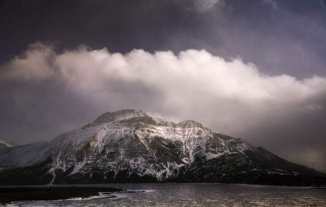 Clouds above snowcapped mountain at Waterton Lake — Stock Photo
