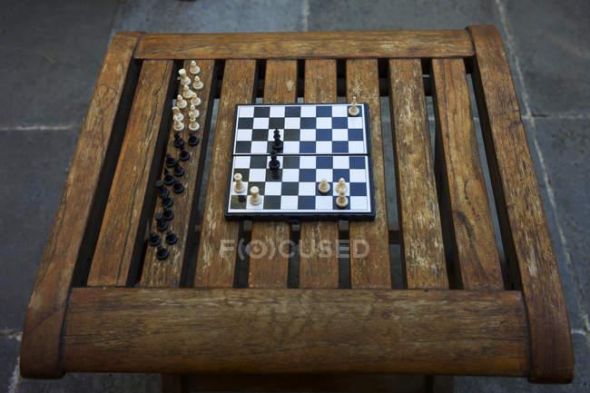 Tabuleiro de xadrez na mesa de madeira na rua — Fotografia de Stock