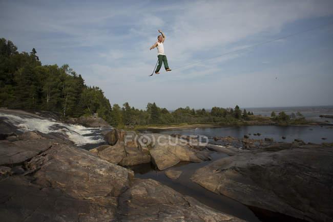Slackliner masculino longa highline a andar sobre a água — Fotografia de Stock